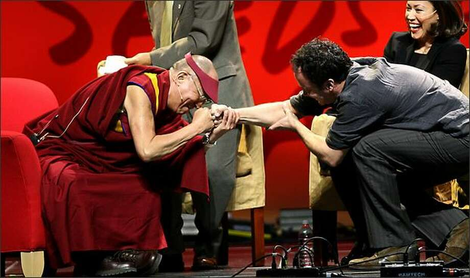 His Holiness the Dalai Lama bumps fists with musician Dave Matthews. Photo: Scott Eklund/Seattle Post-Intelligencer