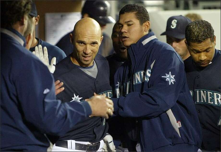 Raul Ibanez is welcomed back into the dugout after hitting his second solo home run against the Los Angeles Angels during fourth inning action at Safeco Field. Photo: Mike Urban/Seattle Post-Intelligencer