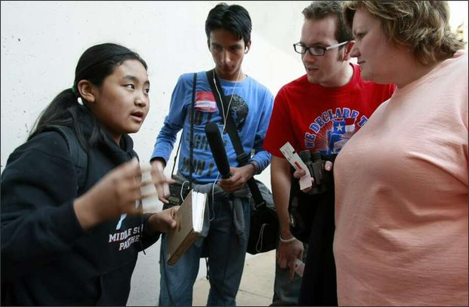 Tenzin Lhamo, 13, from the Tibetan Children's Village in Dharamsala, India, left, and Werner Monterroso, 16, second left, from Guatemala City, interview Judy Smith, right, and son Josh from Flower Mound, Texas, at KeyArena on Friday. Photo: Meryl Schenker/Seattle Post-Intelligencer