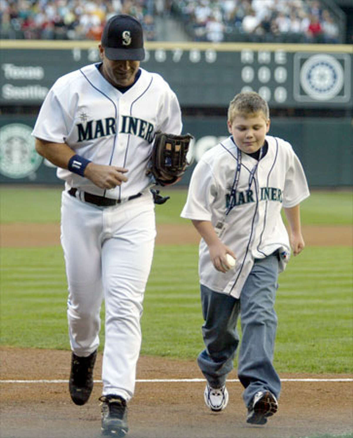 Mariners Edgar Martinez and his son Alex leave the field after throwing the ceremonial first pitch before the game against the Texas Rangers.