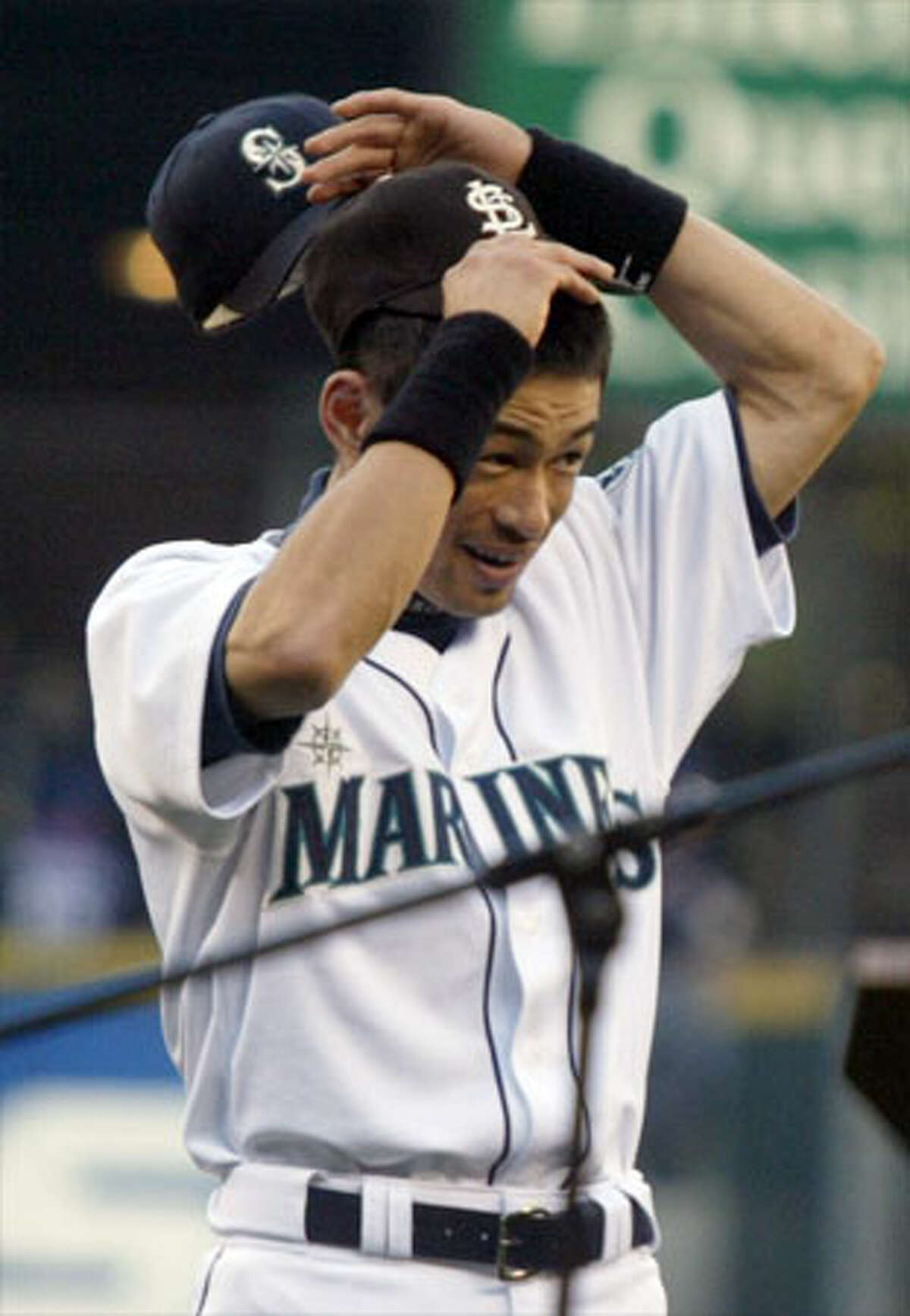 Mariners Ichiro Suzuki puts on an autographed George Sisler baseball hat during a ceremony prior to the game against the Texas Rangers.