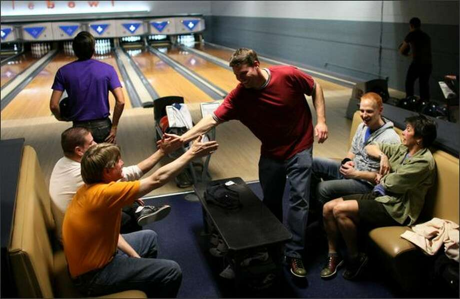 Bowler Matt Woods, center, gets a high-five from teammate Wylie Summerlin after knocking down all the pins during league bowling Thursday at West Seattle Bowl in Seattle. The bowling alley has put in swanky features to draw a new generation of customers. Photo: Joshua Trujillo/Seattle Post-Intelligencer