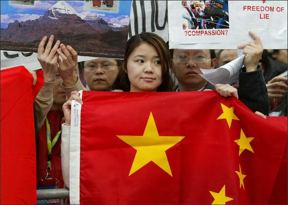 Pro-Chinese protestors, including Ting Ting Xiao, center, show their disapproval of the Dalai Lama and the news media's coverage of the Tibetan conflict before the religious leader was to receive an honorary degree at the University of Washington. Photo: Joshua Trujillo/Seattle Post-Intelligencer