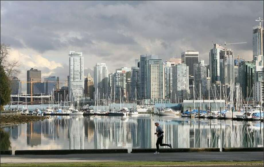 Vancouver high-rises loom across the water as a man jogs along Coal Harbor in Stanley Park. Photo: DAN DELONG/P-I