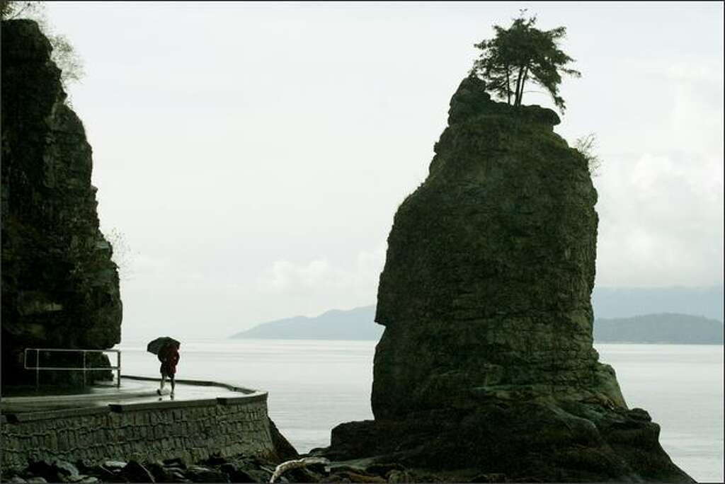 A man huddles under his umbrella as he walks past Siwash Rock along Stanley Park's Seawall. Photo: DAN DELONG/P-I