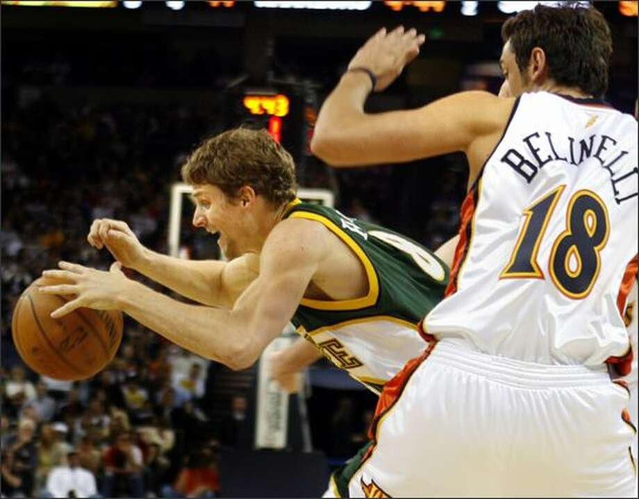 Luke Ridnour, left, gets tripped up by the Warriors' Marco Belinelli (18) in the first half. Photo: / Associated Press