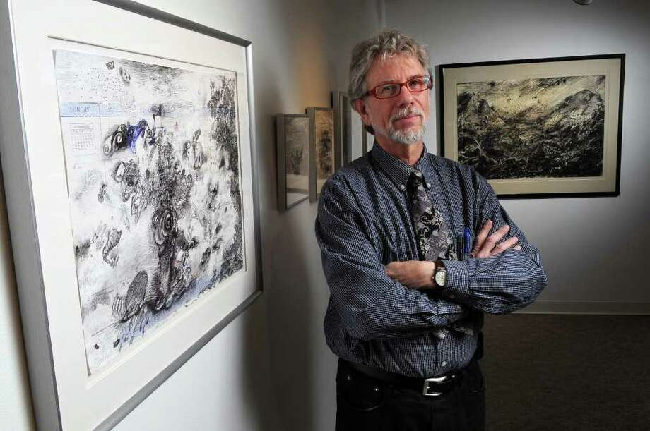 "Artist Charles Steckler stands next to ""Hanukkah Begins at Sundown,"" a mixed media drawing on a calendar page, part of an exhibit of his work at the Arts Center of the Capital Region, on Tuesday March 15, 2011 in Troy, NY.  Behind him at right is his work, ""Imaginary Alpine Landscape in a Storm."" ( Philip Kamrass / Times Union ) Photo: Philip Kamrass"