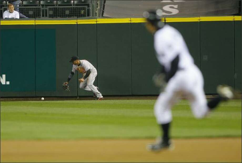 Ichiro Suzuki makes his way to second as Baltimore's right fielder Nick Markakis chases a ground ball. Photo: Gilbert W. Arias/Seattle Post-Intelligencer