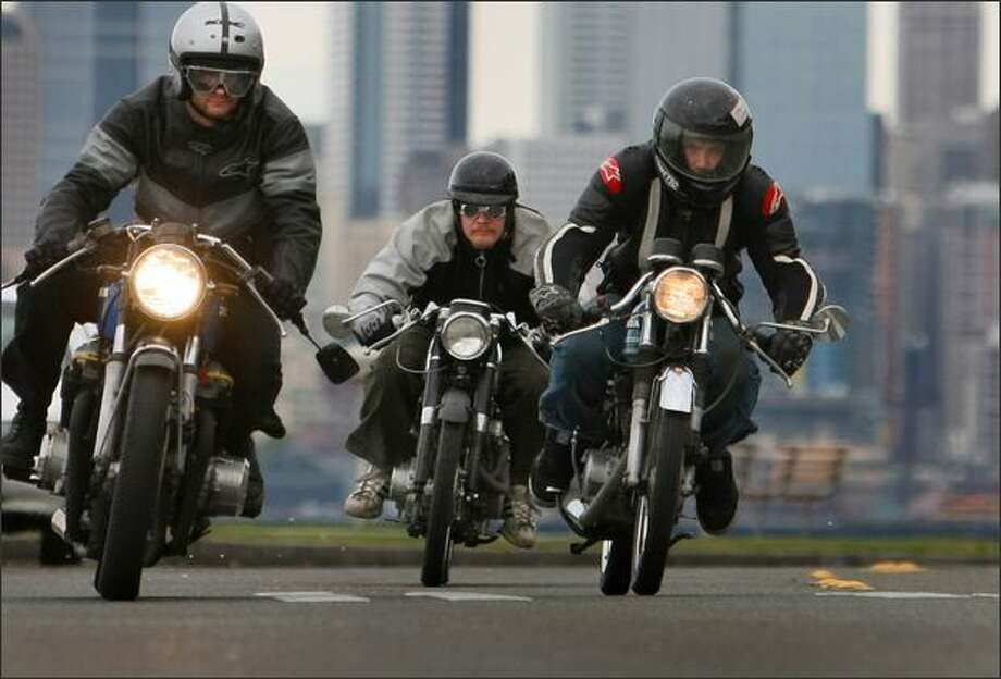Motorcycle enthusiasts, from left, Ian Halcott, Brandon Gillam and Isaac Siegl cruise along Alki Beach. The trio work at Twinline Motorcycles. Photo: Joshua Trujillo/Seattle Post-Intelligencer