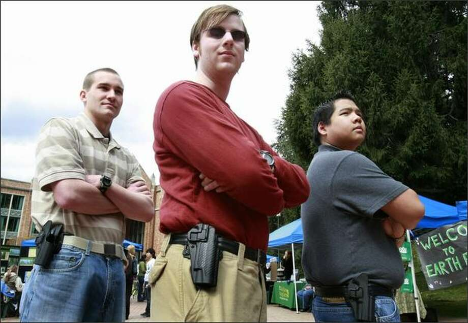 From left, Sean Carhart, Bill Fowler and Brian Yip, all University of Washington students, pose with empty holsters, symbolizing their belief that concealed weapons should be allowed on campus. Photo: Meryl Schenker/Seattle Post-Intelligencer