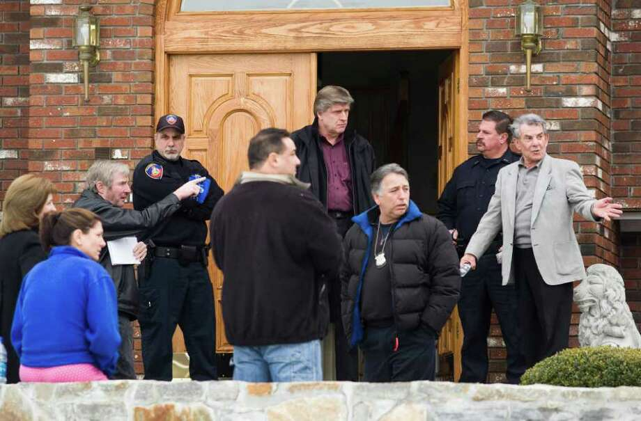 Stamford Police talk with homeowners at 20 Brushwood Road in North Stamford as they investigate a report of a home invasion in March 2010. FBI and Stamford police arrested homeowner Nick Melia at the house Wednesday. Photo: File Photo / Stamford Advocate File Photo