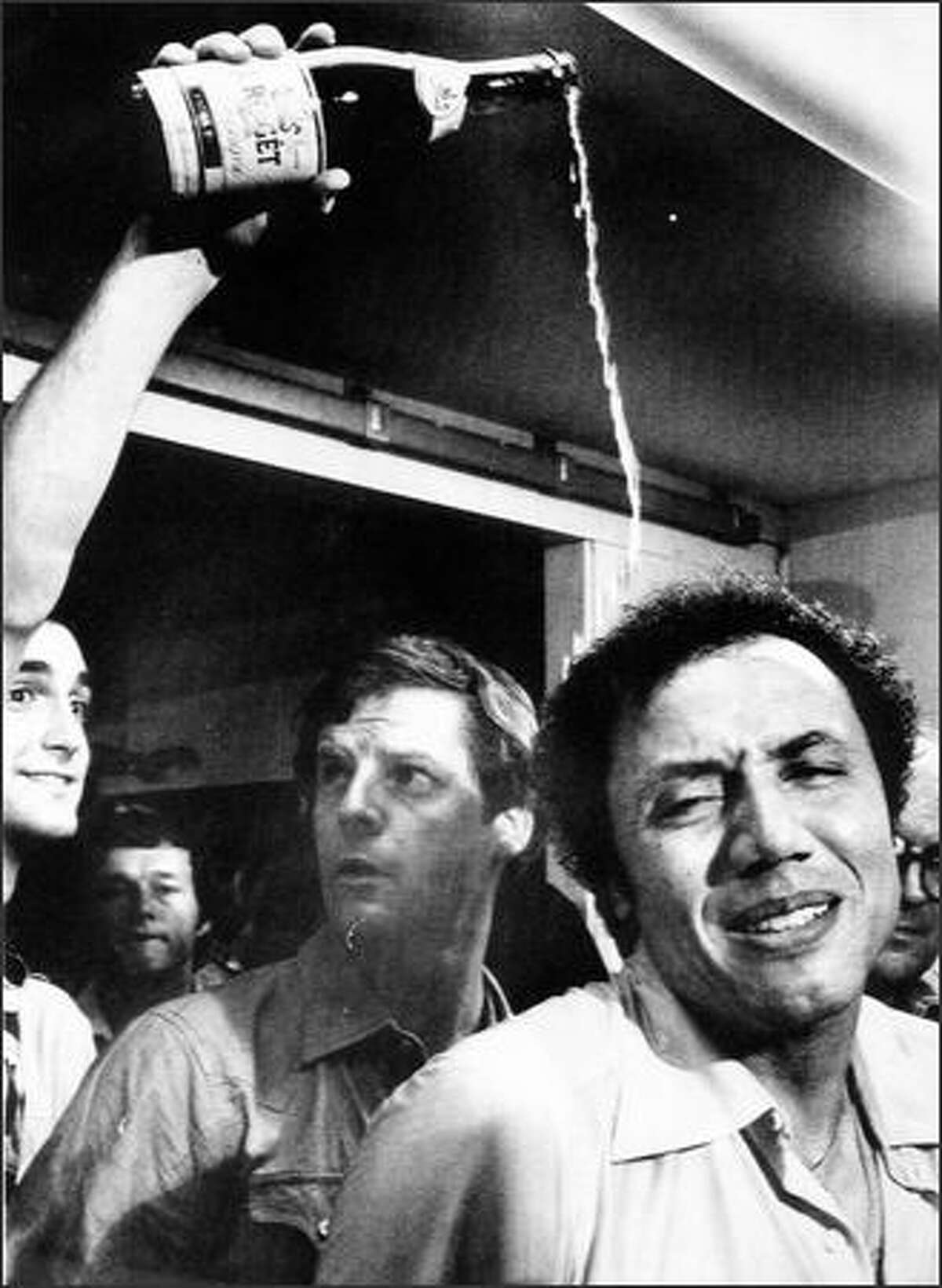Supersonics head coach Lenny Wilkens tries to smile as champagne is poured over his head in the dressing room in Landover, Md., after the Sonics beat the Washington Bullets on June 1, 1979 ,for the NBA national championship.