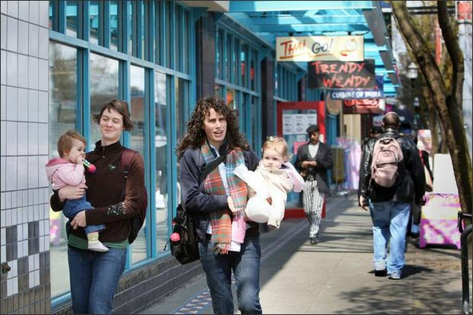 Lizzie Knudsen, right, with daughter Mable, walks down Broadway with Katie Duerr and daughter Eva on Friday. Both live elsewhere, but still visit Capitol Hill. Photo: Karen Ducey/Seattle Post-Intelligencer