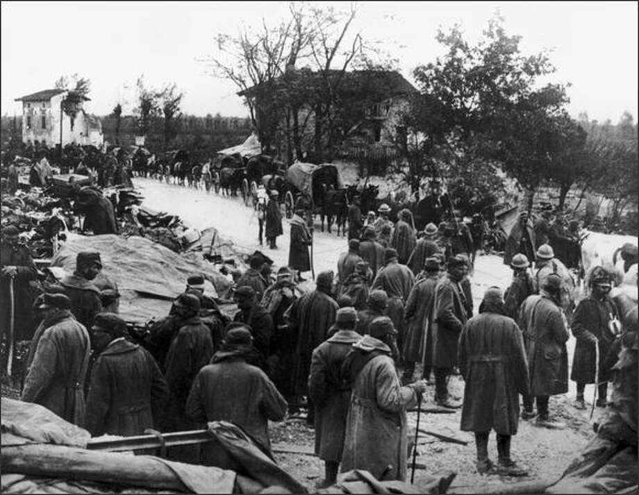 """Italian troops retreat along the Udine-Codroipo Road in north-east Italy after being soundly defeated by Austro-Hungarian and German forces at Kobarind in the Soca Valley, November 1917. The retreat was famously described in Hemingway's novel """"A Farewell to Arms"""" and today is commemorated in Europe's most celebrated anti-war museum, the Kobariski Muzej. Photo: / Getty Images"""