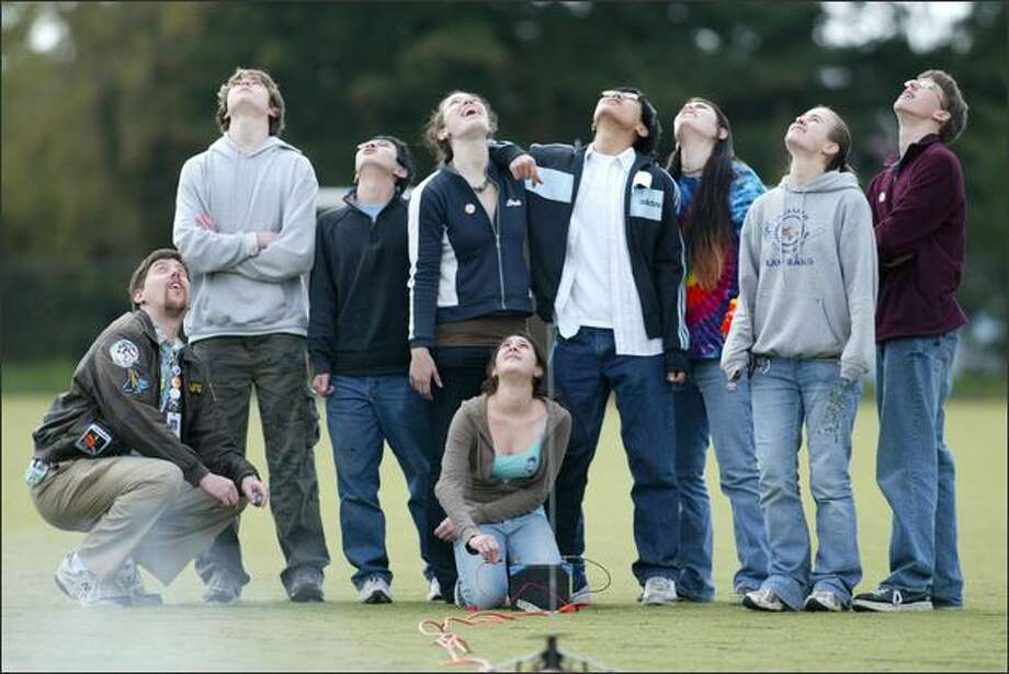 Members of the Ingraham High School rocketry club keep their eyes on one of their creations. From left are teacher Peter Schurke, Nat Mote, Patrick Ma, Sarah Crane, Alex Kon, Nelly Nicklason, Kim Smith and Julian Picard. Kneeling is Katy Loubet-Senear. Club members must chase the rocket down after it returns to earth by parachute. Photo: Grant M. Haller/Seattle Post-Intelligencer