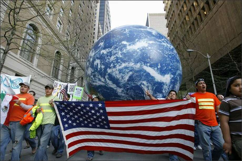 Demonstrators participating in the annual May Day March carry a giant globe up 4th Ave in downtown Seattle. Photo: Gilbert W. Arias/Seattle Post-Intelligencer