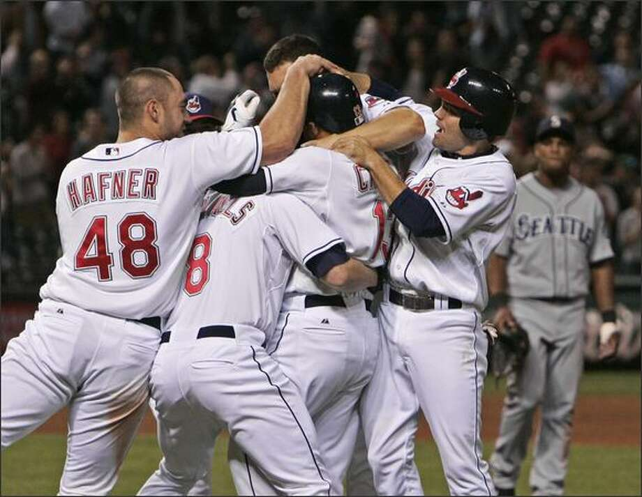 Cleveland's Travis Hafner (48), Jason Michaels (8), Jamey Carroll, right, and others pile on Asdrubal Cabrera (13) after his bases-loaded single off Mariners relief pitcher Mark Lowe in the 11th inning gave the Indians a 3-2 win. Photo: / Associated Press