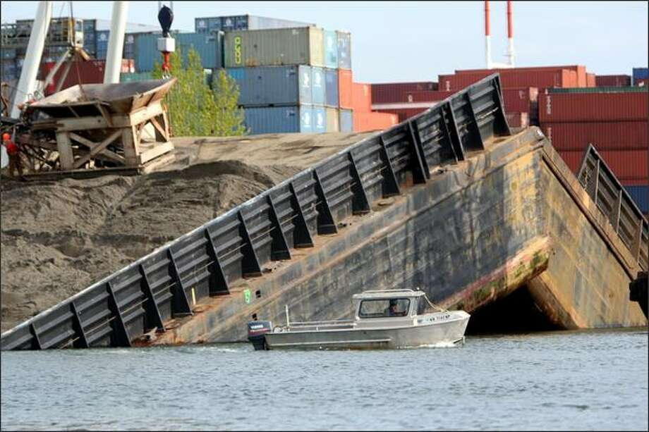 A boat cruises past a barge that broke apart while crews were unloading gravel about 4 p.m. Friday. Photo: Karen Ducey/Seattle Post-Intelligencer