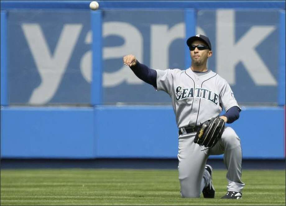 Mariners left fielder Raul Ibanez flips the ball back to the infield after committing an error that allowed Hideki Matsui to advance to second base on a base hit in the third inning. Photo: / Associated Press