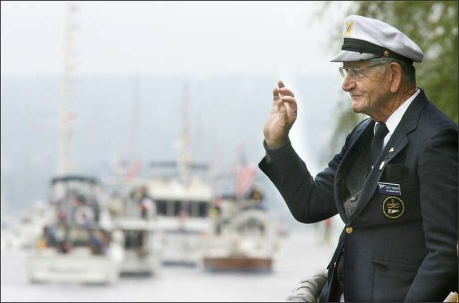 """Dave Romano of Seattle, past Seattle Yacht Club commodore (1990-91), flashes a boat the OK sign during the """"Parade of Boats."""" Photo: Dan DeLong/Seattle Post-Intelligencer"""