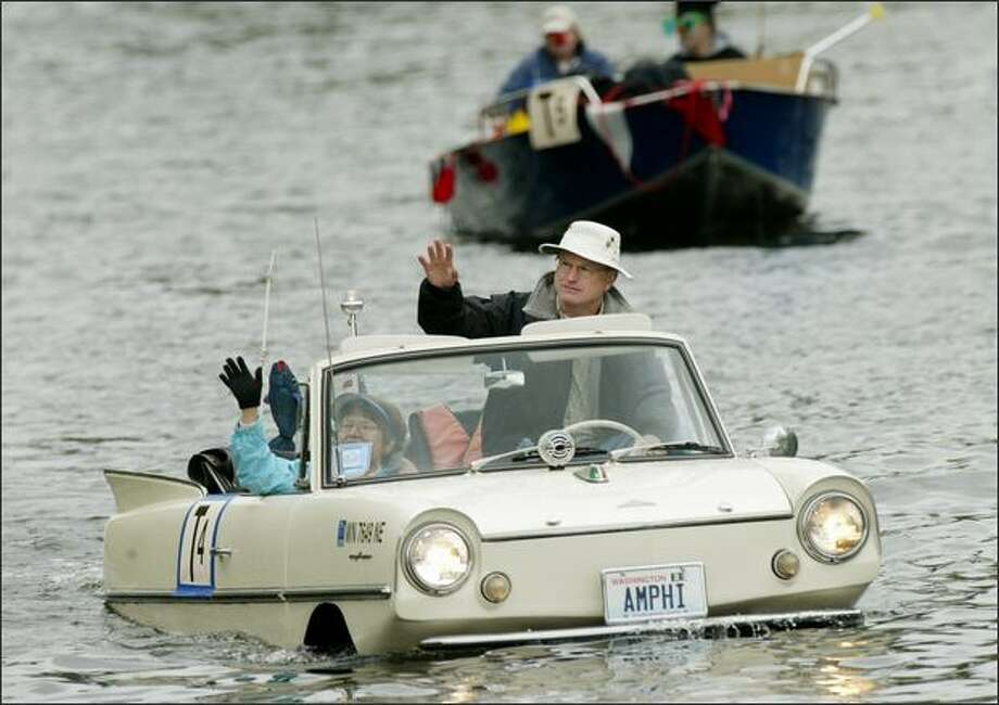 "Larry and Nancy Solheim wave from their 1966 Amphicar during the Opening Day ""Parade of Boats"" on the Montlake Cut in Seattle. Photo: DAN DELONG/P-I"