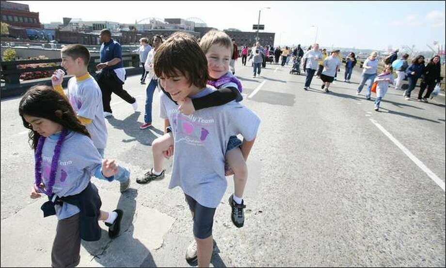 Joey Alonzo, 12, carries nephew Adrian Alonzo, 5, born 15 weeks early, on the Alaskan Way Viaduct during Sunday's  March For Babies, a 3.5-mile fundraiser for the March of Dimes. Photo: Paul Joseph Brown/Seattle Post-Intelligencer