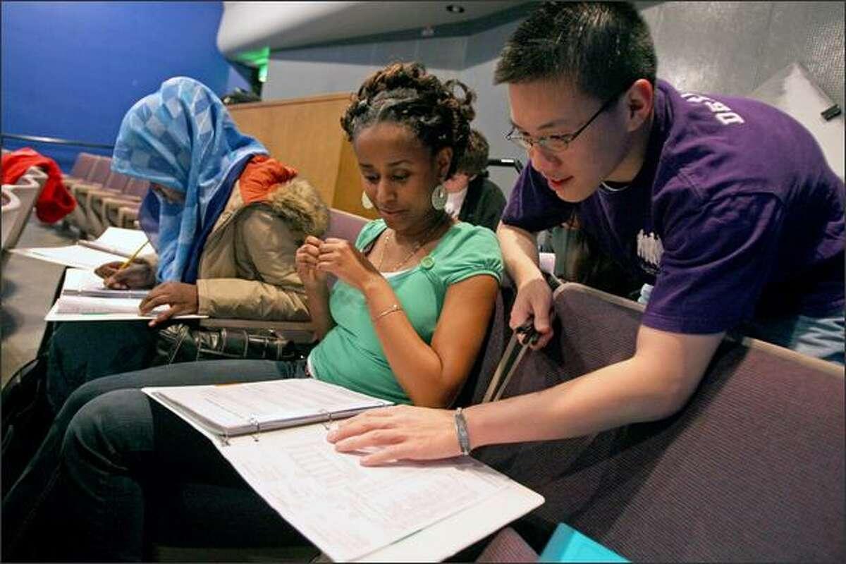 UW sophomore Sam Lim looks over a transcript worksheet with Ingraham High junior Meraf Kifle on Wednesday at the school.