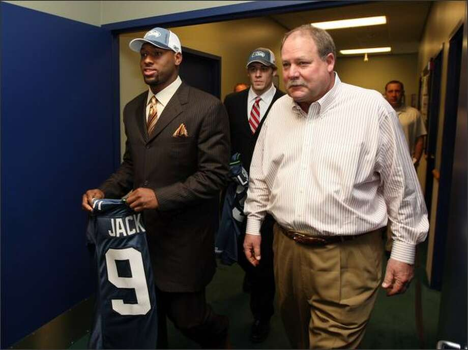 A trimmer Mike Holmgren walks with Lawrence Jackson, left, and John Carlson at a news conference April 28. The coach has dropped 25 pounds. Photo: / Associated Press