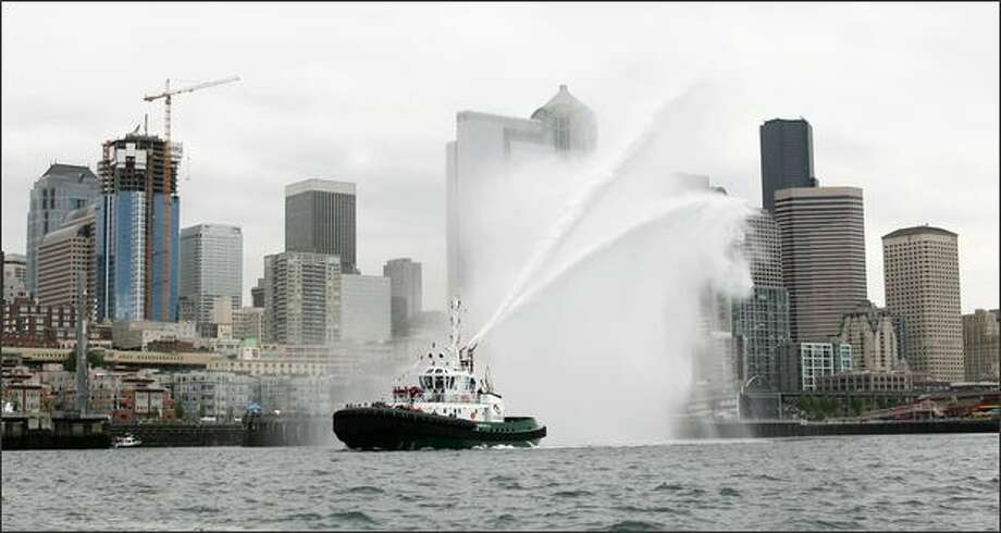 """The tug America, owned by Foss Maritime Company, sprays water during the """"parade to post"""" leading up to the tugboat races. Photo: Dan DeLong/Seattle Post-Intelligencer"""
