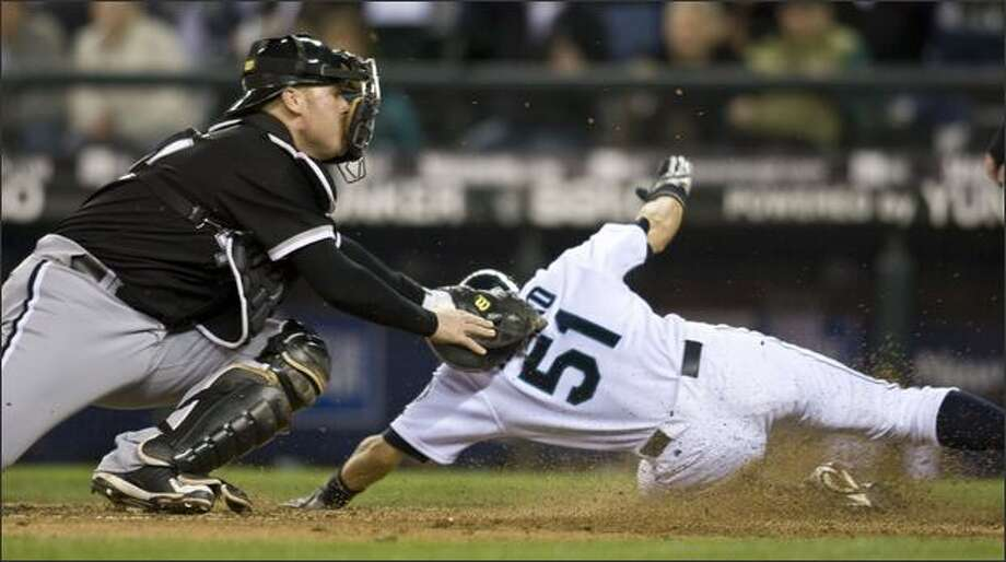 White Sox catcher Toby Hall tags out Ichiro Suzuki at home to end the seventh inning. Photo: / Associated Press
