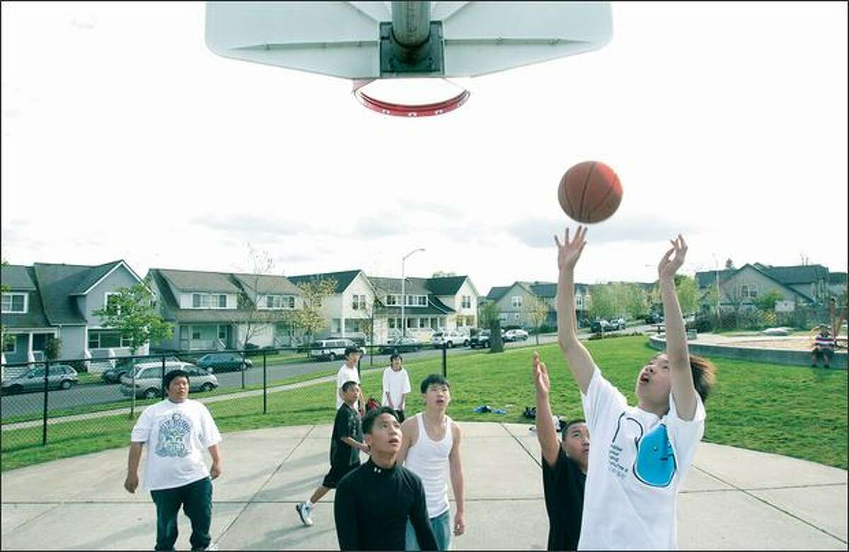 Teenage boys play basketball at Shaffer Park in the New Holly neighborhood campus in Seattle.