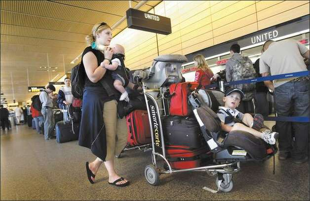 Two-year-old Devon Roeder has a thousand-yard stare as he waits in a long check-in line in his booster seat while his mother, Sandy, feeds his baby brother, Nathaniel, at Sea-Tac Airport on Thursday. Photo: Andy Rogers/Seattle Post-Intelligencer