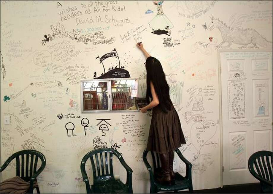 "Author Paula Yoo signs her name on a wall in All For Kids Books next to other signatures. Some, she giggled, were ""famous -- like Academy Award winners of kids books."" Photo: Karen Ducey/Seattle Post-Intelligencer"