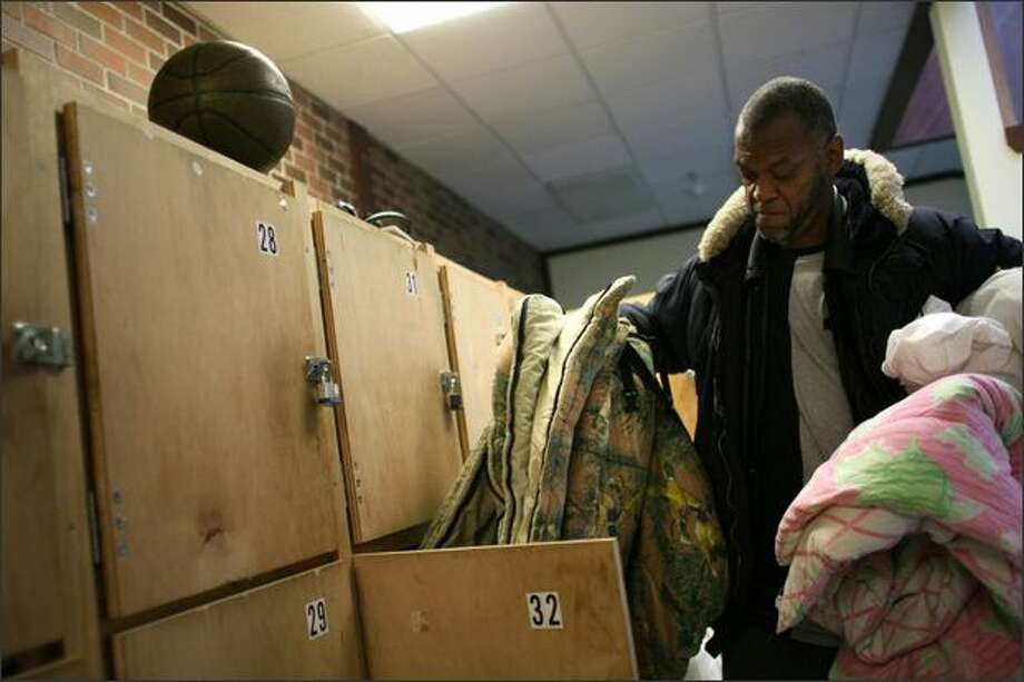 Former NBA champion Joe Pace gets his bedding ready for the night at the Family and Adult Service Center, where he sleeps. He has a small locker there where he stores his blankets and a basketball. Photo: Joshua Trujillo/Seattle Post-Intelligencer