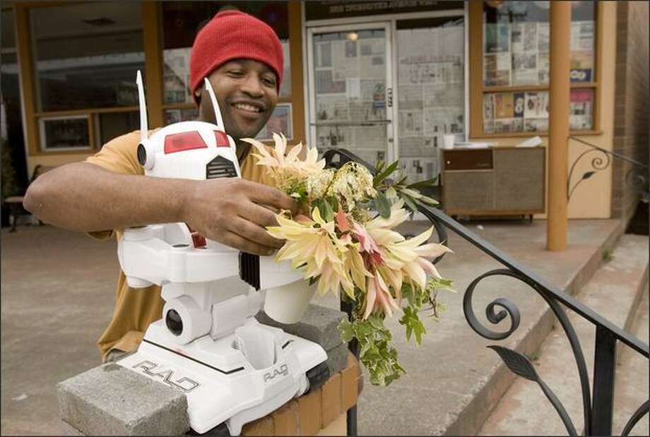 Patrick Mouton cleans out some dead leaves from a cup of flowers someone added to his robot in front of his Brewhaha Coffee Shop at 2818 Thorndyke Ave. W. Wednesday, May 14, 2008. Seattle. Photo: Grant M. Haller/Seattle Post-Intelligencer