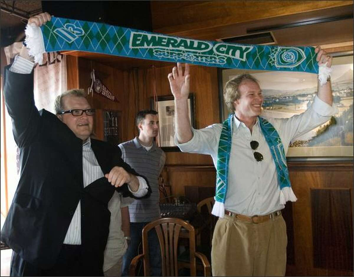 Drew Carey, left, and Tom Challinor wave an Emerald City Supporters scarf Friday.