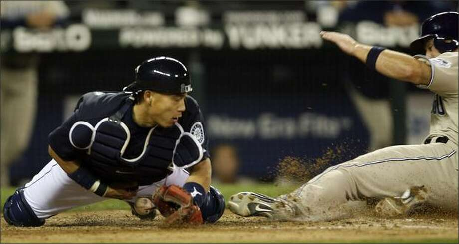 Seattle Mariners Kenji Johjima drops the ball as San Diego Padres Justin Huber slides into home during ninth inning action at Safeco Field. Despite the drop Huber was called out. Photo: Mike Urban/Seattle Post-Intelligencer