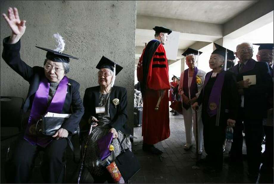 Takako Yoda gives her tassel a playful flip while waiting to enter the University of Washington's Kane Hall for a ceremony Sunday honoring Japanese-American students who were forced to leave the school and live in internment camps in 1942. With her is Miyo Shantaku, and at center is Todd Mildon, registrar at the UW. Photo: Paul Joseph Brown/Seattle Post-Intelligencer