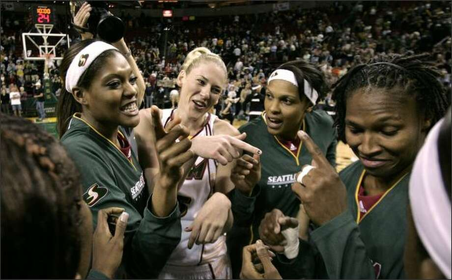 From left, Ashley Robinson, Lauren Jackson, Kelly Santos and Yolanda Griffith share congratulations with teammates in a post-game huddle after beating the Monarchs 74-62. Photo: / Associated Press