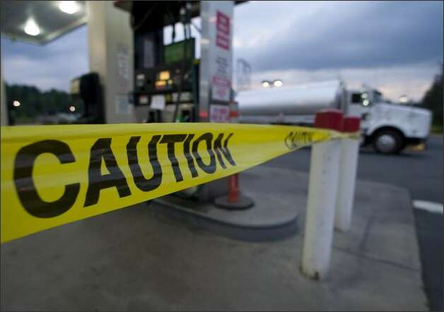 Yellow caution tape warns motorists not to use the gas pumps at the Safeway Gas Station at 27020 Maple Valley Highway Sunday. A number of cars stalled out after purchasing contaminated fuel from the station. Photo: Jim Bryant/Seattle Post-Intelligencer