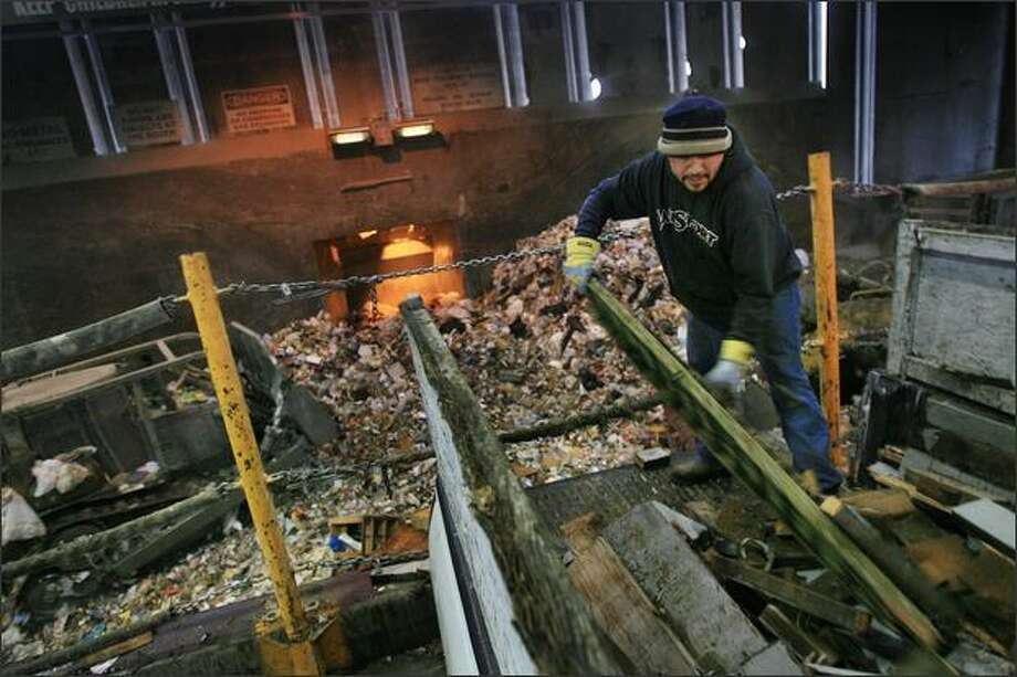 Waste lumber is unloaded at Seattle Public Utilities' South Park garbage transfer station. New buildings will sport ventilation systems that will curtail stinky overflow to neighbors downwind. Photo: / P-I File
