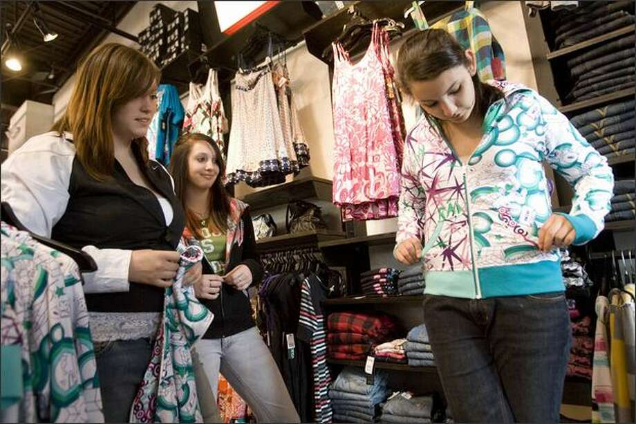 Kelsey Mills, 17, tries on Mix & Match Hoodies, which have zippers in the front and back to allow mixing and matching, with Rachel Wordon, 17, left, and Danielle Bowdish, 14, at the Redmond Town Center Zumiez store Wednesday. Wordon and Mills attend Redmond High School, and Bowdish attends Evergreen Junior High. Photo: Grant M. Haller/Seattle Post-Intelligencer