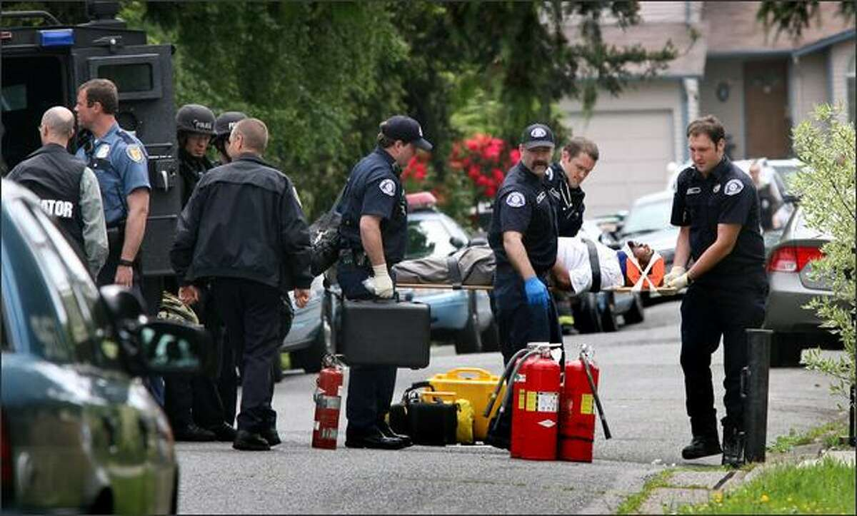 Seattle firefighters carry a man from his Greenwood home Thursday after he surrendered to police. Initial reports, disputed by one of the man's sons, suggested he had doused himself with gasoline.
