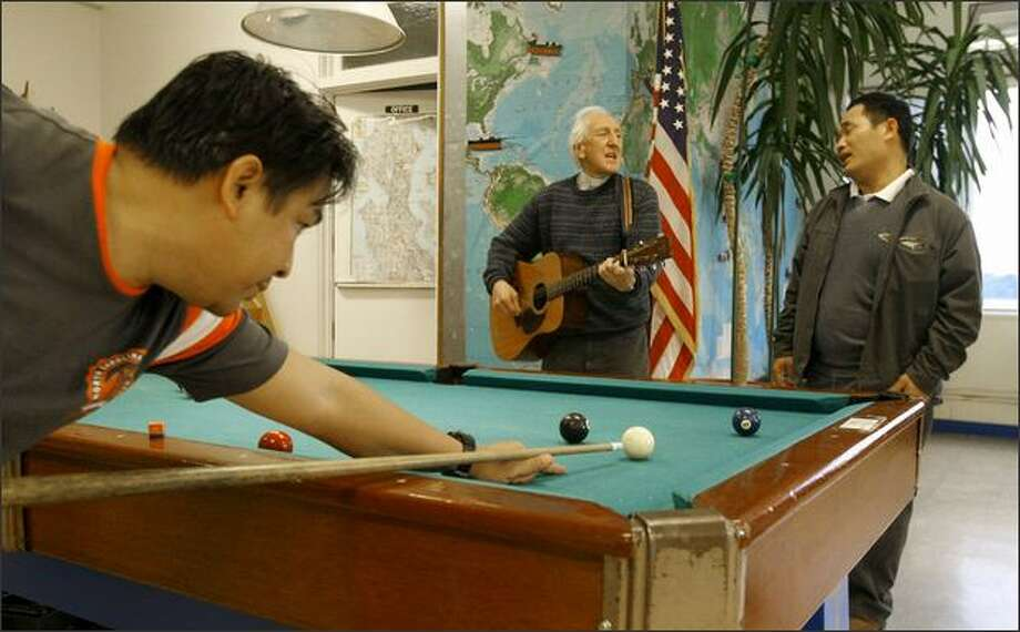 Father Tony Haycock, center, sings with Wesley Kuan, captain of the cargo ship M.V. Sparna, while crewman Daniel Brecio shoots pool at the Catholic Seamen's Club, which has offered recreation and low-cost meals to merchant mariners in Belltown since 1939. Photo: Gilbert W. Arias/Seattle Post-Intelligencer
