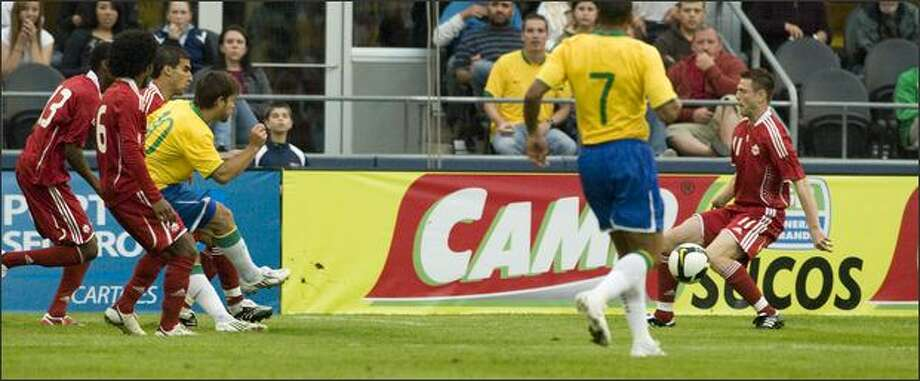 Brazil's Diego (10) fires from a crowd past Richard Hastings (11) for a goal in the first half of an international friendly soccer match Saturday night at Qwest Field in Seattle. Photo: Grant M. Haller/Seattle Post-Intelligencer