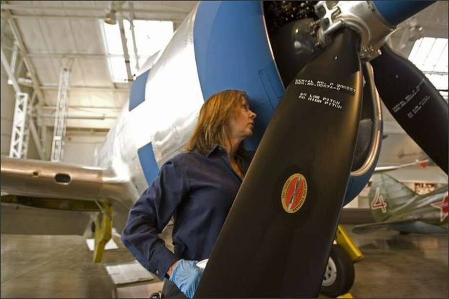 Diane Krivitsky, A&PIA (Airframe & Power Plant Inspection Authorization) mechanic checks behind the prop of a Republic P-47D Thunderbolt as she gets the plane ready for the opening of the collection. Photo: Grant M. Haller/Seattle Post-Intelligencer