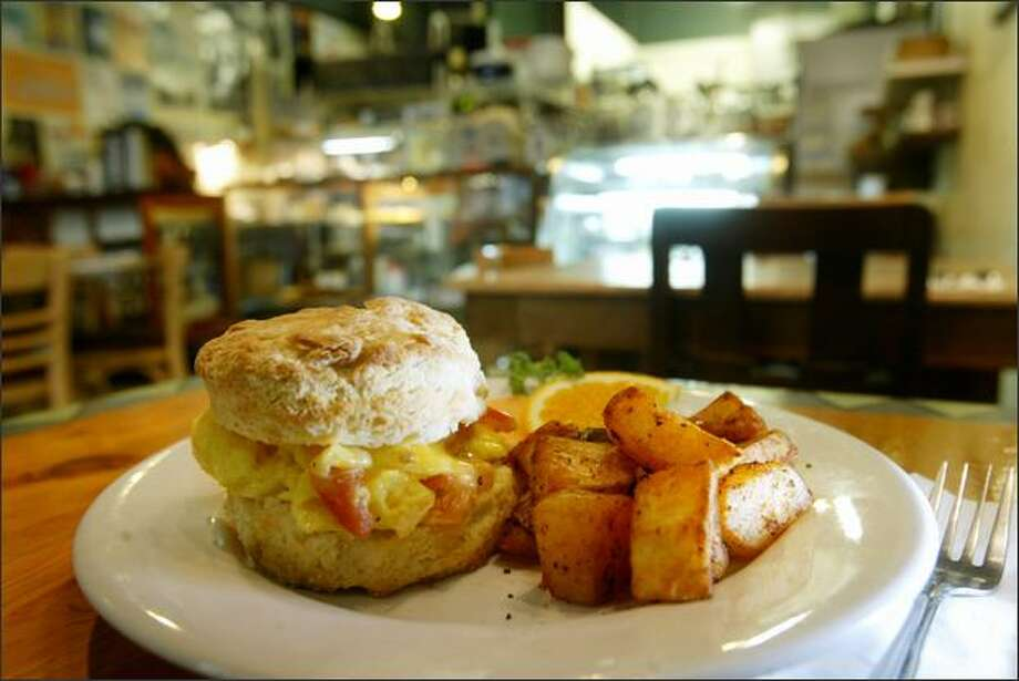 The buttermilk biscuits are divine. Here they sandwich scrambled eggs, cheddar cheese and tomatoes; served with house-roasted potatoes. Photo: Dan DeLong/Seattle Post-Intelligencer