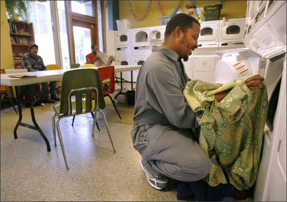 Darrell Williams does a load at Urban Rest Stop, which offers free laundry services, restrooms and showers to the homeless. Photo: Kristine Paulsen/Seattle Post-Intelligencer