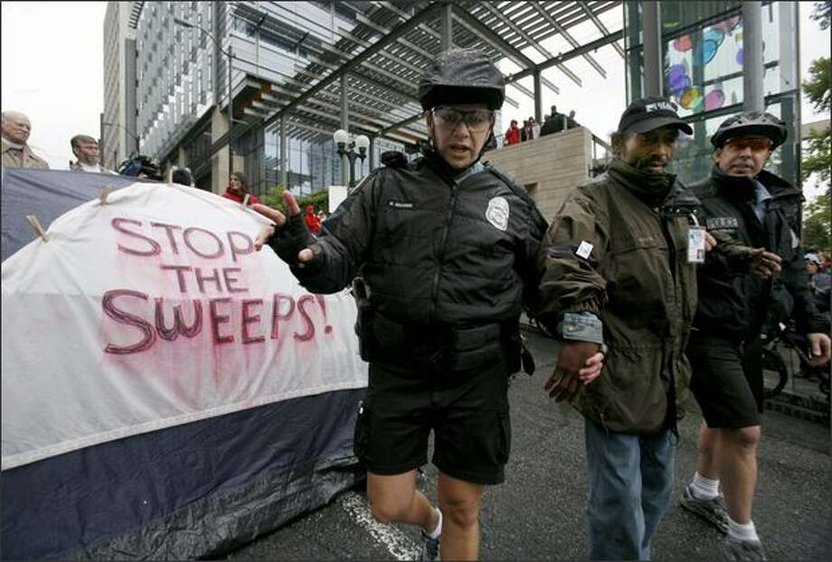 Seattle police officers arrest Calvin Turner for disrupting traffic during a protest by homeless people and advocates at Seattle City Hall. Photo: Paul Joseph Brown/Seattle Post-Intelligencer