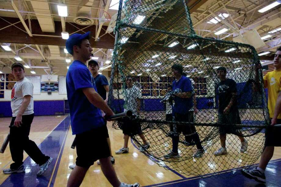 The Westhill High School baseball players Jack Grafstein, left, and Tim Longo carry a batting net through the gym where they practice in Stamford, Conn., March 23, 2011. The team will not be able play on their home field this season because dugouts are not ready for season. Photo: Keelin Daly / Stamford Advocate